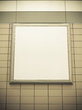 Empty blank square white advertising billboard on tiled wall Royalty Free Stock Photo