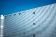 Blank billboard steel frame on facade of industial style building under blue sky Royalty Free Stock Photo