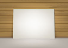Empty Blank White Mock Up Poster Picture Frame Standing on Floor with Brown Sienna Wooden Wall Front View Royalty Free Stock Photo