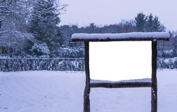 Empty and blank wooden advertisement board covered in snow, winter season in the forest, publicity billboard. A empty and blank wooden advertisement board royalty free stock photo