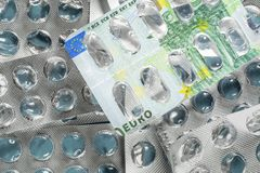 Empty blister pack of pills with 100 euro banknote picture. Medical concept of expensive treatment in Europe. Empty blister pack of pills with 100 euro bill royalty free stock photos