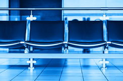 Empty blue airport seats bench bokeh background Royalty Free Stock Photography