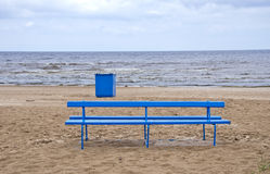 Empty blue bench and rubbish box on sea beach Stock Photo
