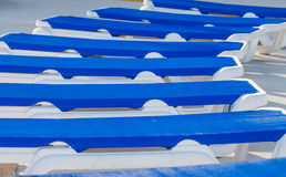 Empty Blue Chaise Lounges. Blue vinyl chaise lounges in a patio around a swimming pool stock photos
