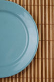 Empty Blue Dish. On the bamboo background Stock Image