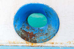 Empty blue hawse in old rusted ship hull Stock Photo