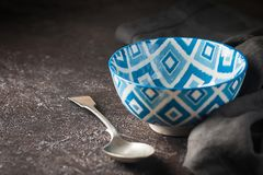 Empty blue oriental bowl. With a spoon on dark stone background Royalty Free Stock Photography
