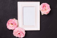 Empty  blue photo frame and pink roses flowers on black  texture Royalty Free Stock Photo