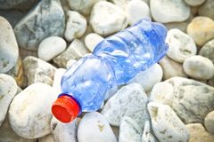 Empty blue plastic bottle with red cap on gravel beach.  stock image