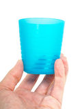 Empty blue plastic glass, held in a male persons hand Stock Photography