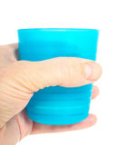 Empty blue plastic glass, held in a male persons hand. Isolated on white royalty free stock photo