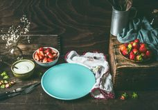 Empty blue plate on dark rustic wooden kitchen table with strawberries and yogurt in bowls. Country style food background. With berries , still life. Place for stock image