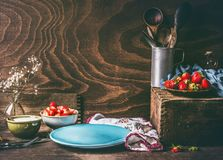 Empty blue plate on dark rustic wooden kitchen table with strawberries and yogurt in bowls. Country style food background. Still life. Place for your design royalty free stock photos