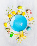 Empty blue plate and easter eggs decoration with daffodils , chicken,and table sign on gray wooden background, top view. Copy space Royalty Free Stock Photos