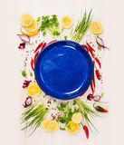 Empty blue plate with fresh seasoning and spices on withe rustical wooden background, top view. Place for text Royalty Free Stock Photos
