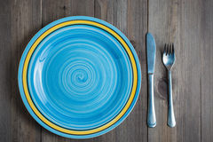 Empty blue round plate with fork and knife on dark wooden background. Empty blue turquoise round plate with fork and knife on dark wooden background view from Stock Photography