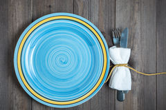 Empty blue round plate with fork and knife wrapped in white napkin on dark wooden background. Empty blue turquoise round plate with fork and knife wrapped in Stock Photos