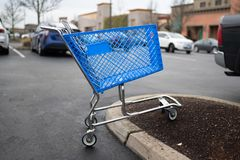 Empty blue shopping cart on the parking lot royalty free stock photo