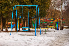 Empty blue swing and children playground in winter park, outdoors Royalty Free Stock Image