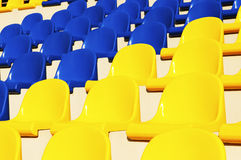 Empty blue and yellow seats in stadium Royalty Free Stock Images