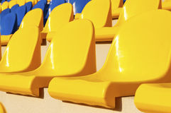 Empty blue and yellow seats in stadium Stock Image