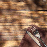Empty board with fork and knife on wooden table. Top view Stock Photo