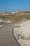 Empty boardwalk curves through a sandy beach. On a sunny day stock images
