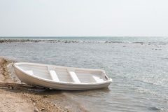 Empty boat on a deserted beach Royalty Free Stock Photos