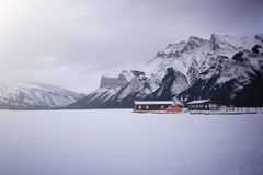 Empty boat dock on frozen lake covered by snow in high mountains, Lake Minewanka, Banff national park, Canada Royalty Free Stock Image