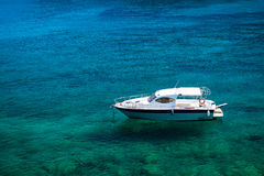 Empty boat floating on clear turquoise water Royalty Free Stock Image
