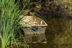 Empty boat. And its reflection in quiet water in forest Stock Photo