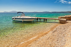 Empty boat standing at wooden pier under bright sunlight Stock Photo