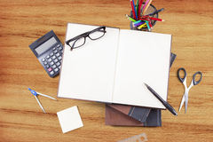 Empty book with stationery on wood table Royalty Free Stock Photography