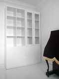 Empty bookcase shelves in white. House interior with a brand new tall white elegant wooden bookshelves in the corner of the room and a piano beside it. Vertical Stock Photos