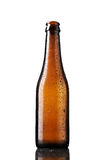 Empty bottle of beer with drops Stock Images