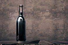 Empty bottle on dark background. Single empty beer bottle placed on wooden desk on dark concrete background. Alcohol drink beverage logo advertisement concept Stock Images