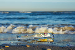 Empty bottle lying in the surf Stock Photography