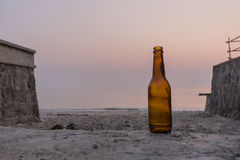 Empty bottle on the seashore Stock Images