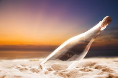 Empty Bottle on a shore. At sunset Royalty Free Stock Image