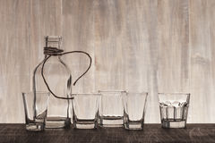 Empty bottle and shots on the bar counter. Empty bottle and shots on the wooden bar counter Royalty Free Stock Photos