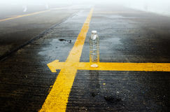 Empty bottle on yellow line in the rain and fog Stock Photography