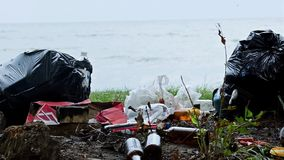 Empty bottles and containers polluting seashore, tons of garbage damaging nature. Stock photo stock photos