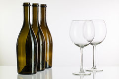 Empty bottles of wine on a glass desk Royalty Free Stock Photos