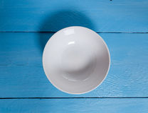 Empty bowl on blue wooden bird's eye view Royalty Free Stock Photo
