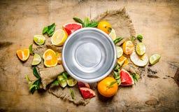 Empty the bowl of fruit around citrus - grapefruit, orange, tangerine, lemon, lime the old fabric. Stock Photos