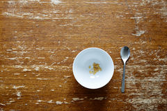 Empty bowl with little cereal on dark wooden table. 