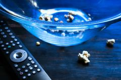 Almost empty bowl of popcorn and TV remote stock image