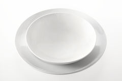 Empty Bowl on a Round Plate Against White Stock Image