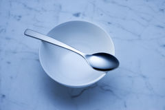 Empty Bowl And Spoon Background. A stylised image of an empty white bowl and spoon on a white marble surface with a blue tone Royalty Free Stock Photo