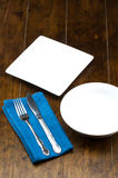 Empty bowl and square dish with fork, knife, napery on wood table. Stock Image